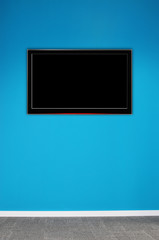Tv on blue wall.