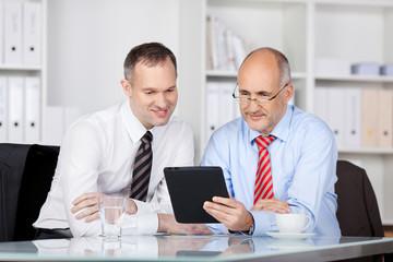 zwei geschäftsmänner schauen auf den tablet-pc
