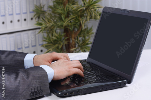 Person Typing on a modern laptop in an office