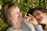 A girl with Down syndrome and her sister laughing in the grass.