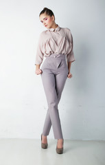 Fashion model female in light trousers and shirt standing