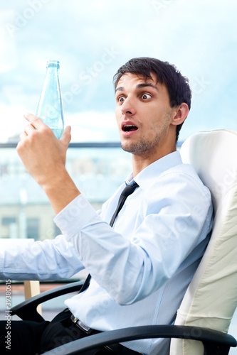 Young business man drinking water sitting relaxed on armchair