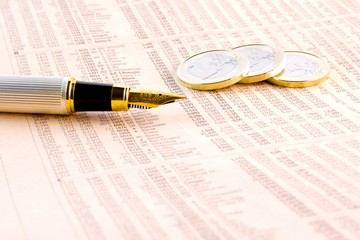 euro coins and a golden pen  on the financial newspaper