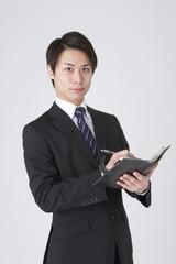 手帳を確認するビジネスマン