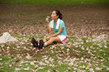 Pretty Thai woman looking flower after exercise .