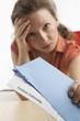 Junge Frau mit Kündigungsschreiben blickt verzweifelt