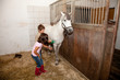 Boy and Girl Grooming a Horse