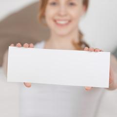 lachende junge frau zeigt weiße karte