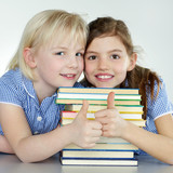 Two cute girls love reading at school and show thumps up