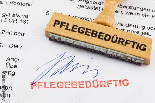 Holzstempel auf Dokument: pflegebedürftig