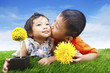 Boy kissing his sister in spring