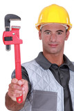 Man with a heavy duty adjustable pipe wrench