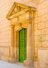 Green door made of wood, in Barcelona city center in Spain