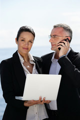 Businesswoman with laptop next to a collaborator on phone