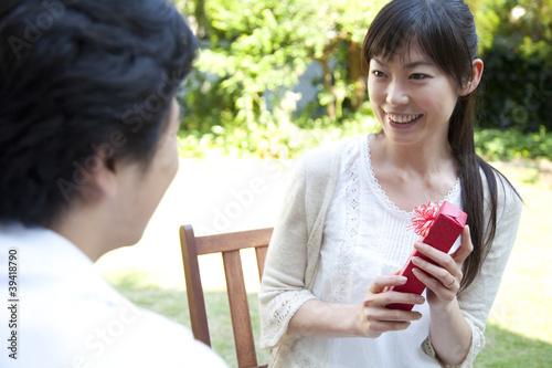 男性からプレゼントを受け取り喜ぶ女性