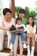 ソファに座り本を読む家族