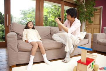 ビデオカメラで娘を撮る父親
