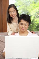 ノートパソコンを一緒に見る父親と娘