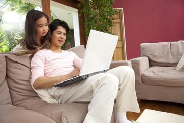 ノートパソコンのモニターを見る父親と娘