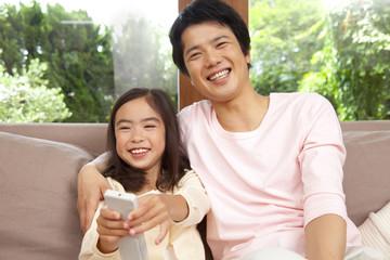 リモコンのスイッチを押す娘と父親