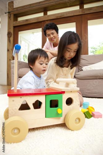 手押し車で遊ぶきょうだいと見守る父親