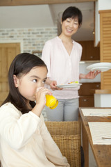 食事を運ぶ母親とオレンジジュースを飲む娘