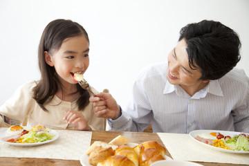 娘に朝食を食べさせる父親