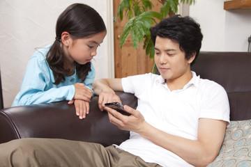 スマートフォンを見る父親と娘