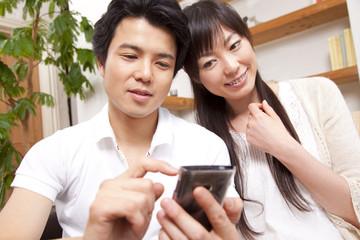 スマートフォンを見るカップル