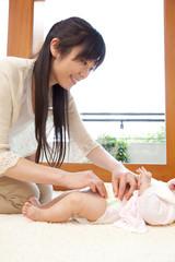 赤ちゃんのオムツをかえる母親