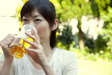 庭でビールを飲む女性