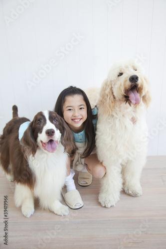 ゴールデンドゥードルとイングリッシュスプリンガースパニエルを抱き寄せる笑顔の女の子
