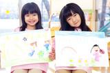 絵を持って微笑む幼稚園女児2人