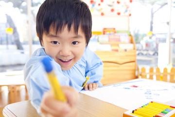 クレヨンを手に持っておどける幼稚園男児