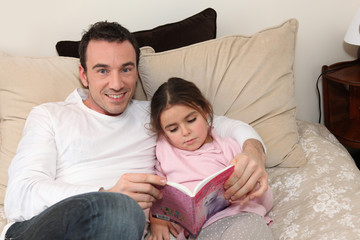 Father reading to his daughter