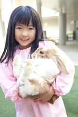 うさぎを抱っこする幼稚園女児