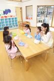 お弁当を食べる幼稚園教諭と幼稚園児