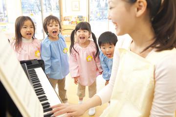 幼稚園教諭のピアノに合わせて歌う幼稚園児