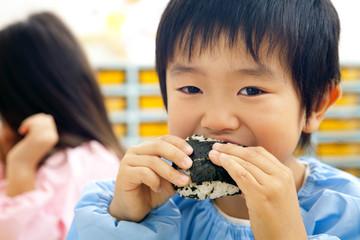 おにぎりを食べる幼稚園男児