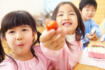 お弁当を食べながらおどける幼稚園児