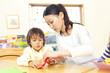 折り紙を折る保育園児と保育士