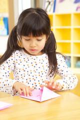 折り紙を折る保育園児