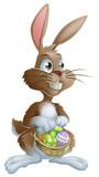 Fototapety Easter bunny rabbit holding Easter eggs basket