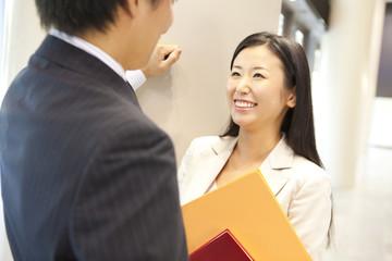 笑顔で会話するビジネスマンとOL
