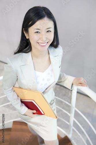 階段をのぼる笑顔のOL