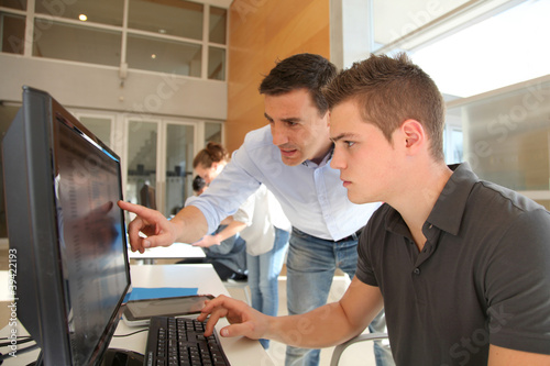Leinwandbild Motiv Teacher and student working on computer