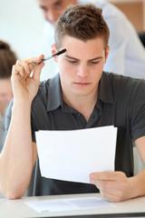 Portrait of student boy doing written exam