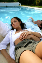 Couple lying at poolside