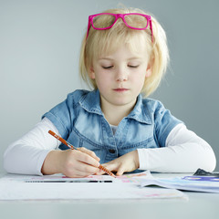 Cute child with glasses in her hairs is doing her homework