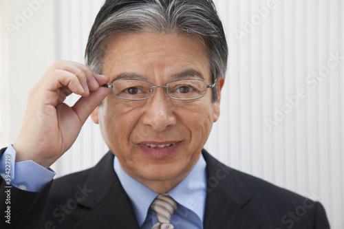 眼鏡のフレームを掴むビジネスマン